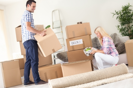 unpacking:  A young couple unpack moving boxes.