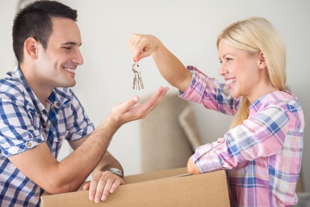 새 집으로 젊은 행복 한 커플, 여자 집 열쇠를 들고와 그녀의 남자 친구를주는 이동