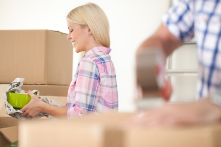 moving out:  Women packing some household things in moving boxes