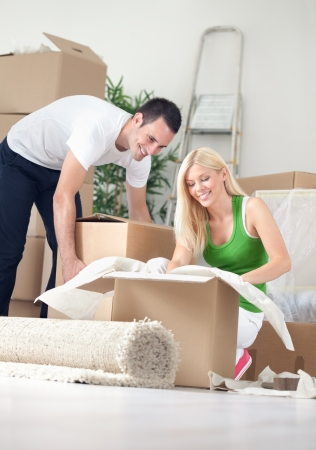 moving out:  Cheerful couple in new home, unpacking boxes