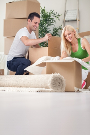 Merry young couple unpacking boxes in their new house photo
