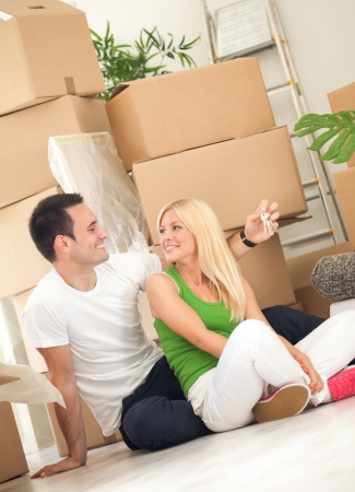 Couple moving into new home with door keys and boxes photo