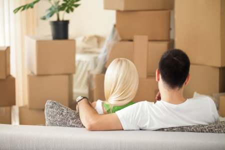 new: Couple looking at cardboard boxes in her new home, back view Stock Photo