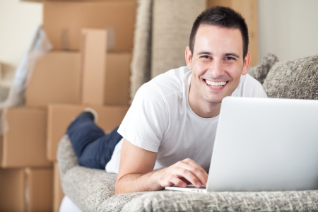 Happy young man using laptop in his new home photo