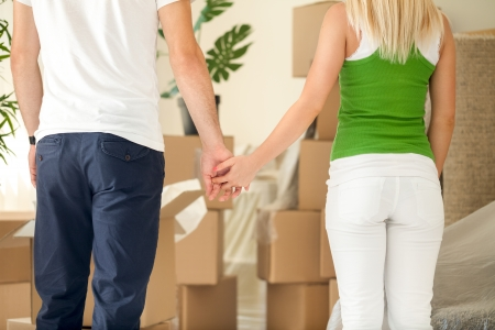 first move: Couple with cardboard boxes moving into a new house and holding hands Stock Photo