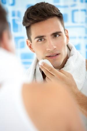 young man standing: giovane uomo in piedi nella sua stanza da bagno dopo la rasatura pulizia del viso con un asciugamano Archivio Fotografico