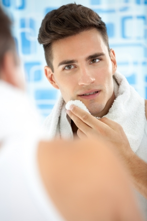 man face: young man standing in his bathroom after shaving cleaning face with a towel
