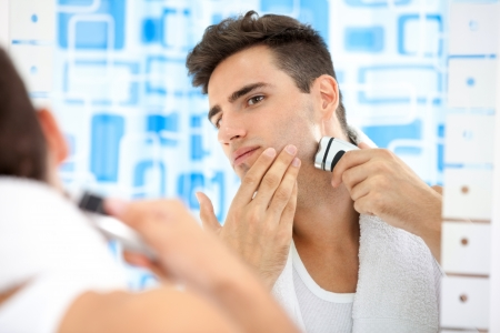 Young man shaving by electric shaver photo
