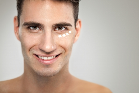 metrosexual:  Portrait of young man with anti- aging cream, skincare