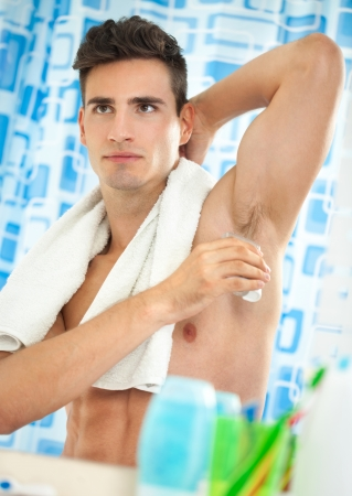 armpits:  Young handsome men applying deodorant on armpits  Stock Photo