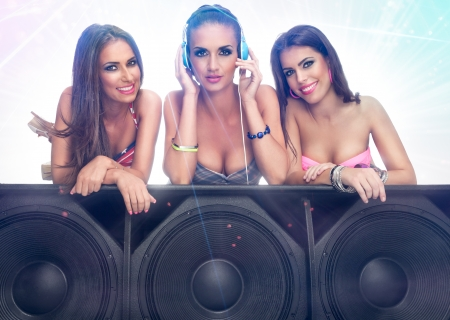 Three cute girls listening music on large speaker photo