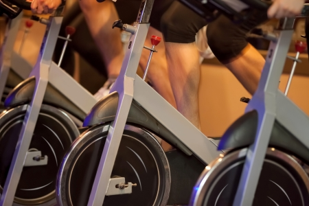 spins:  Group of four people spinning in the gym, exercising their legs doing cardio training
