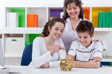 mother with her children putting money in piggybank, family saving  Фото со стока