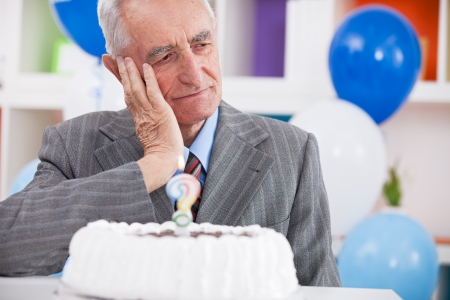 Sad senior man forgot how old is looking at birthday cake with a question mark photo