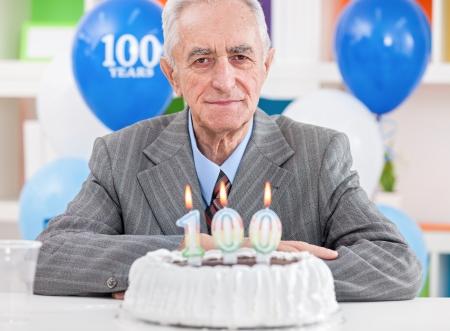 gratifying:  Senior men sitting front of cake for 100th birthday