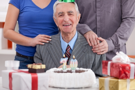 Happy senior man celebrating his 70th birthday with family photo