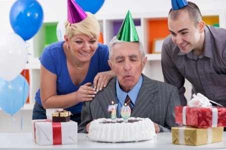 Senior man with family blowing in  the candles on birthday cake photo