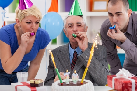 70 year old man:  Happy senior man celebrating birthday with his family