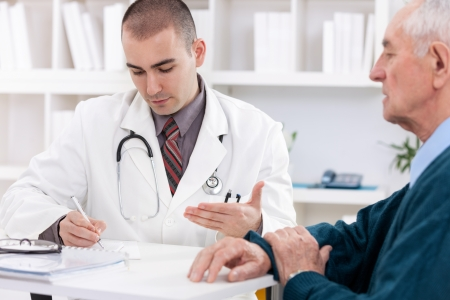 Portrait of handsome male doctor talking with senior patient photo