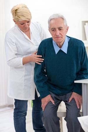 helps:  cheerful nurse helps senior man