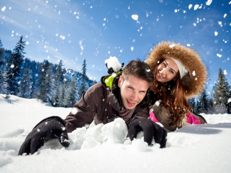 Portrait of joyful woman throwing snowball at man Stock Photo