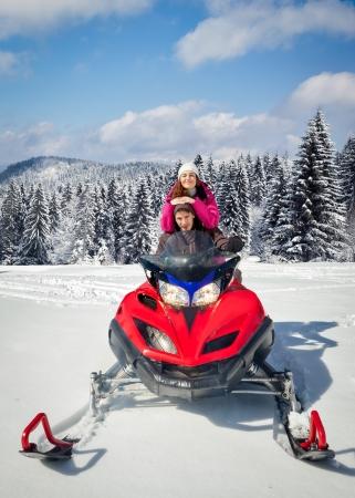 Paar Schneemobil-Fahren im Winter Berg