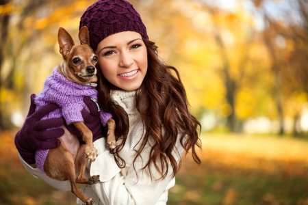 Young woman holding her miniature pinscher puppy after playing in the park photo