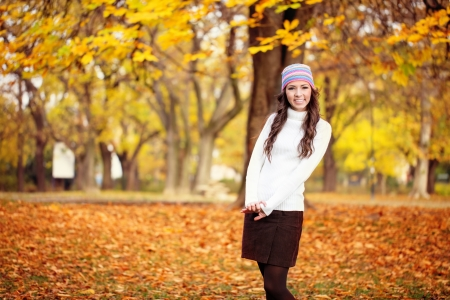 Cute girl in autumn park, posing in season clothing photo
