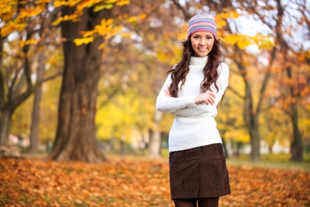 Young woman in autumn park, posing in season clothing photo