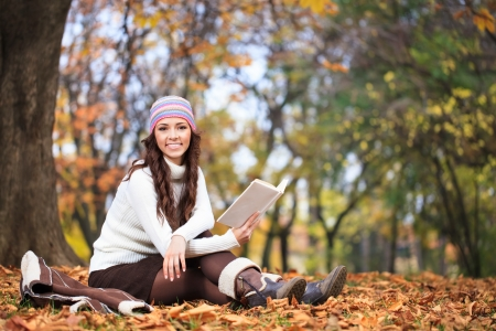 Cheerful woman with book in autumn park, smiling and looking at camera photo