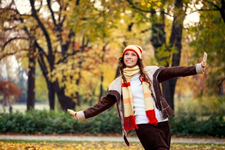 Happy young woman playing  inautumn forest photo