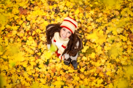 adorable young woman with autumn leaves in the park, top view photo