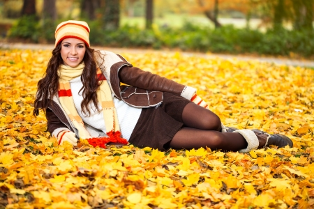 Attractive young woman lying in autumn leaves in park  photo