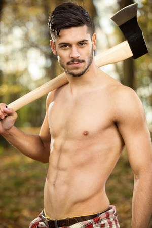 Young fit lumberjack holding an ax over his shoulder photo