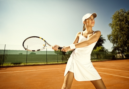 Woman in sportswear plays tennis at training photo