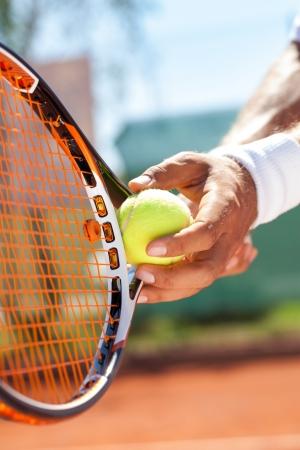 테니스 공을 가진 플레이어의 손에 봉사하는 준비