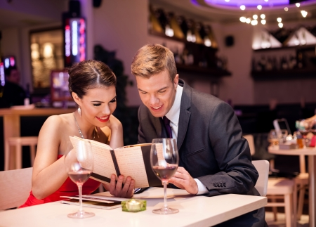 boy romantic: Couple reading menu together and choosing meal Stock Photo