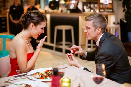 anillo de compromiso: Hombre joven romántico que propone a la novia y ofreciendo anillo de compromiso
