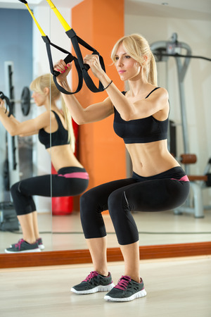 resistance: Young woman doing exercise while hanging on resistance band Stock Photo