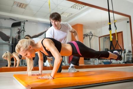 Flickan gör armhävningar med motstånd band i närvaro av en personlig tränare Stockfoto