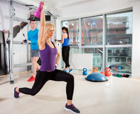 woman lifting weights:  Sporty woman exercising  with kettle bell at gym