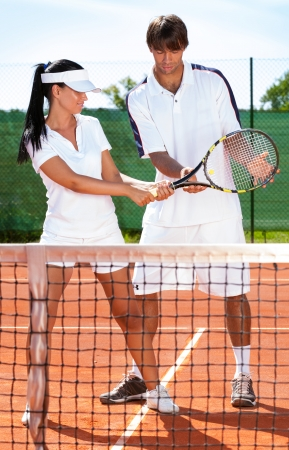 sportswoman with coach practicing tennis photo