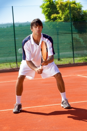 Male tennis player waiting for a service photo
