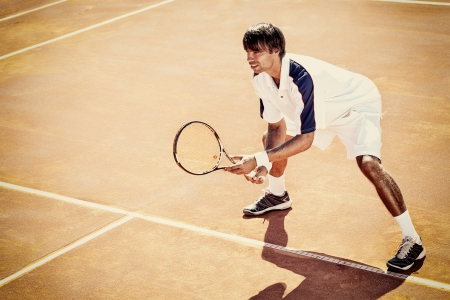 young man play tennis outdoor on orange tennis court  photo
