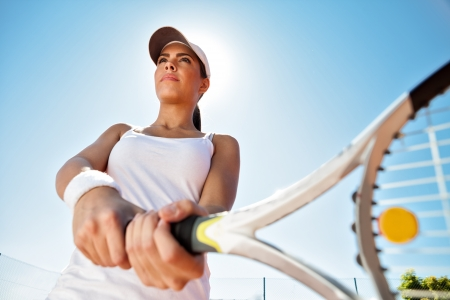 Beautiful sporty girl  with tennis racket playing tennis  photo