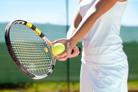 Players hand with tennis ball and racket photo