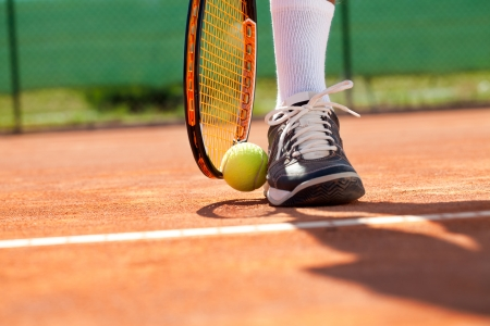 forehand:  Sportsman catches up his tennis ball with racket
