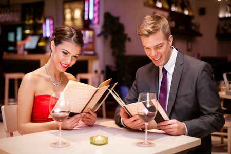 young couple dining in restaurant and reading menu.