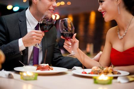 ロマンチックな夕食の間にレストランのテーブルの上のワイングラスを焼くことカップルの手。