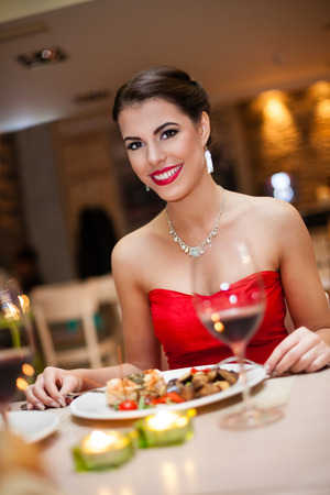 Beautiful young woman in red eating in restaurant